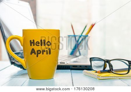 Hello April greeting written on yellow morning coffee or tea cup. Spring time concept at office.