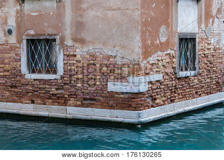 Decayed wall of ancient brick building in Venice, Italy on the edge of the canal