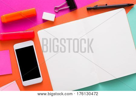 Creative minimal design - flat lay of workspace desk with stationery, mobile smart phone, blank sketchbook or tablet with copy space. Template, mockup, objects