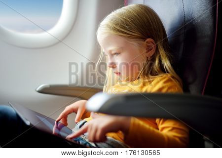 Adorable Little Girl Traveling By An Airplane. Child Sitting By Aircraft Window And Using A Digital