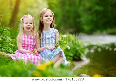 Two Adorable Little Sisters Playing By A River In Sunny Park On A Beautiful Summer Day
