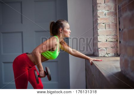 The beautiful healthy girl pumps muscles using dumbbell at the gym