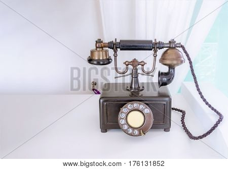 Ancient phone is placed on a wooden table vintage style.