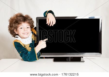 Cute kinky prince embracing television he points his index finger on a blank screen. Gray background.