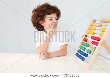 Cute curly-haired boy with a pencil in his hand pressed his index finger to his lips with a grin looking at the analog calculator. Close-up. Gray background.