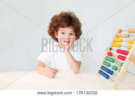 Cute curly-haired boy with a pencil in his hand pensively looking into the camera. Close-up. Gray background.