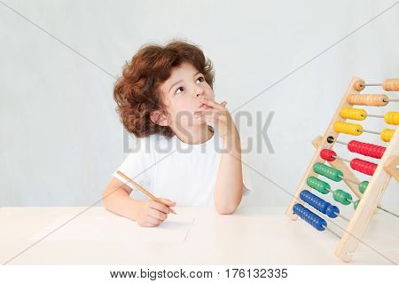 Cute curly-haired boy with a pencil in hand and a scores on the table thoughtfully looking up. Close-up. Gray background.