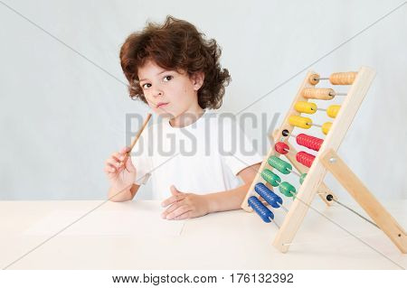 Cute curly-haired boy with pencil in hand looks thoughtfully into the camera. Close-up. Gray background.