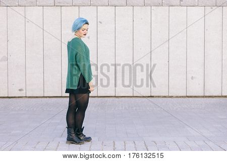 Teen androgynous woman on a sad expression with blue dyed hair isolated on the street wearing a blue sweater.