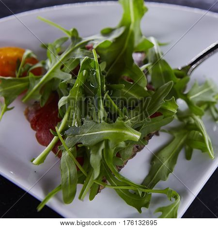 slice of prosciutto or jamon with arugula leafs.