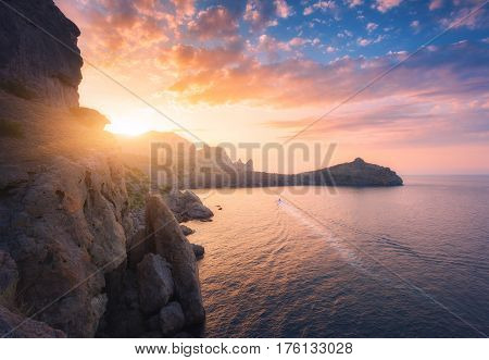 Mountain landscape at sunset. Beautiful view from the hill on the blue sea cape cliffs and colorful sunny sky with orange clouds in the evening. Travel in Europe in summer. Nature background