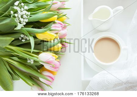 Morning breakfast in spring with a cup of black coffee with milk and pastries in the pastel colors a bouquet of fresh yellow and pink tulips on a white background. Top view.