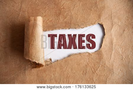 Torn piece of scroll uncovering the word taxes