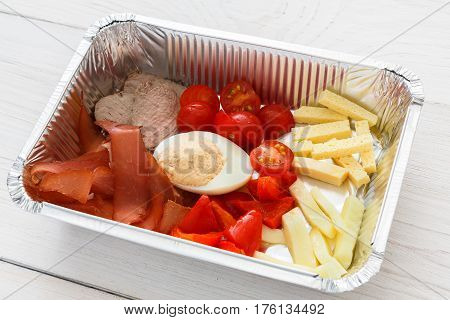 Healthy food in foil box closeup. meat with egg and vegetables, cherry tomatoes and beef. Restaurant dishes delivery, lunch for diet