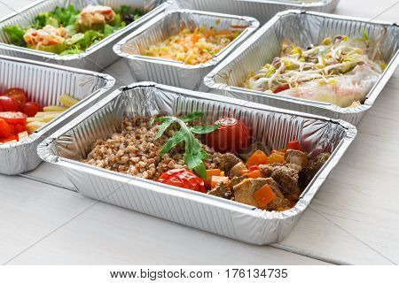 Healthy food background. Take away of natural organic meals in foil boxes. Fitness nutrition, eggs, meat, fresh vegetables and kasha buckwheat porridge. Restaurant dishes delivery
