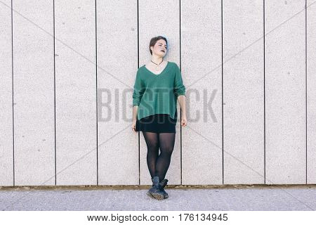Teen androgynous woman with blue dyed hair isolated against a wall wearing a blue sweater.
