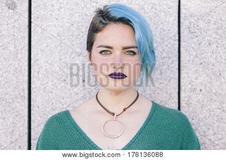 portrait of a confident teen androgynous woman with blue dyed hair isolated on the street wearing a blue sweater.