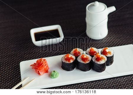 Traditional sushi on a white plate with ginger and wasabi