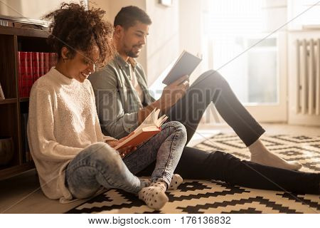 African american couple enjoying reading books at home.