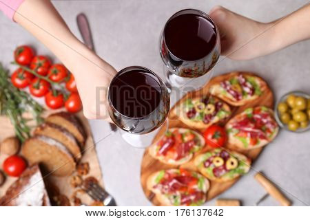 Woman hands toasting with glasses of red wine on gray background