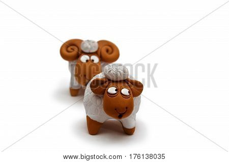 Two white and brown ceramic sheep figurine isolated on white background close up