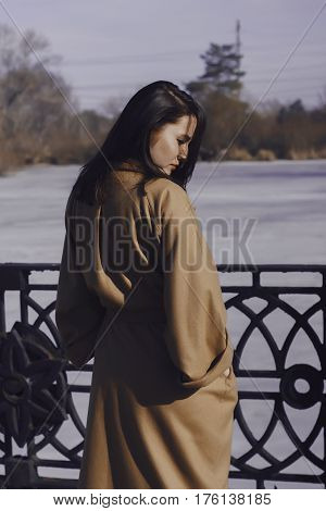 stylish young woman out for a walk. she dressed and looks very fashionable. coat of beige (camel) color and black turtleneck. beautiful woman. She's back at the river.