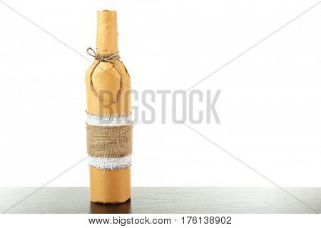 Table with bottle of wine in paper on white background