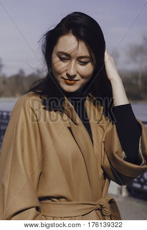 stylish young woman out for a walk. she dressed and looks very fashionable. coat of beige (camel) color and black turtleneck. the portrait she smiles and looking down. girl straightens her hair.