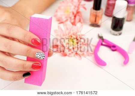 Nail art concept. Beautiful female hand with manicure holding buffer, closeup