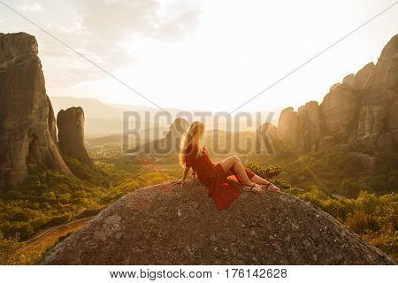 Sexy Girl Sits On The Edge Of The Cliff And Looking At The Sun Valley And Mountains