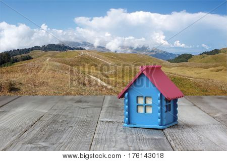small blue wooden house on a background of mountains and sky. cottage in the mountains.