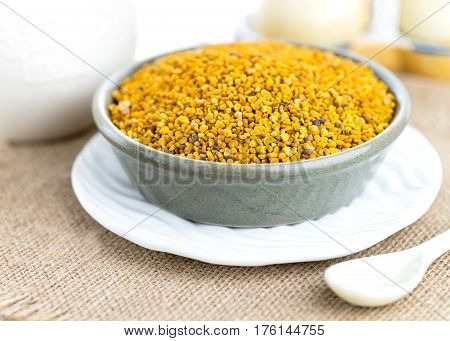 full dish of bees pollen shot in a selective focus contrasting textures in cloth and whit ceramic pottery in the background
