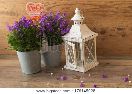 Candlestick lamp and flowers bells campanula on a wooden background.
