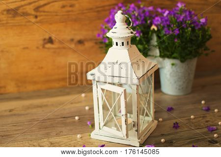 White candlestick. Wicker basket with violet flowers Campanula portenschlagiana and beautiful white pearl on a wooden background.