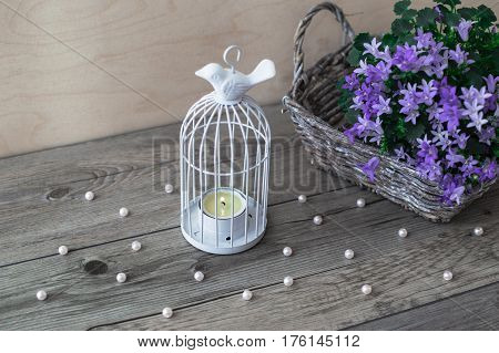 White candlestick. Wicker basket with violet flowers Campanula portenschlagiana and scattered beads of pearls on a gray wooden background.