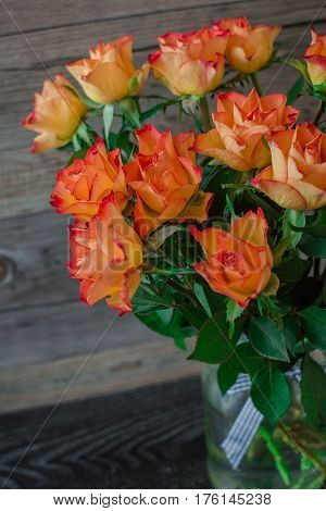 Pretty fresh orange roses on a wooden background. A beautiful bouquet of roses for present.