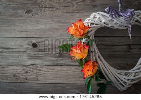 A white heart made of grapevine. Beautiful orange roses on light gray wooden background. Romantic symbol of love.