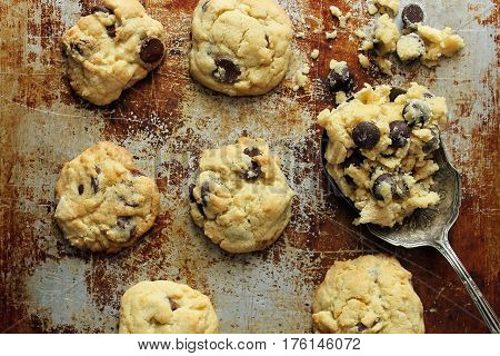 Home made chocolate chip cookies on a tarnished baking sheet with a vintage spoon with dough on it
