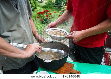 man pours a fish soup from a bowler into a bowl fish soup cooked at the stake fish soup cooking in a pot on a fire