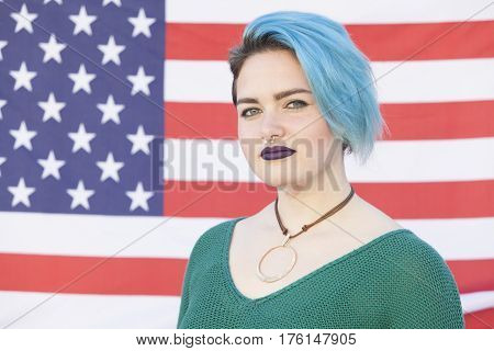 portrait of a young androgynous woman fighting for equality against a United States of America flag