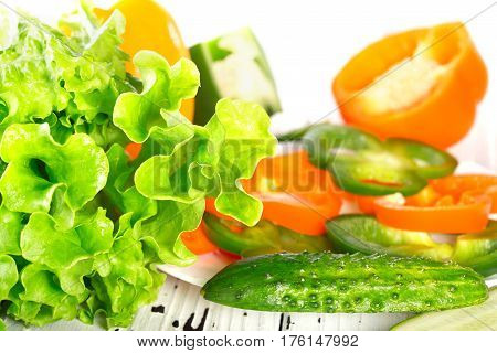 Fresh vegetables on a white background. Sweet pepper a cucumber and green lettuce leaves lie on a white board. Green and orange pepper is cut with rings on pieces