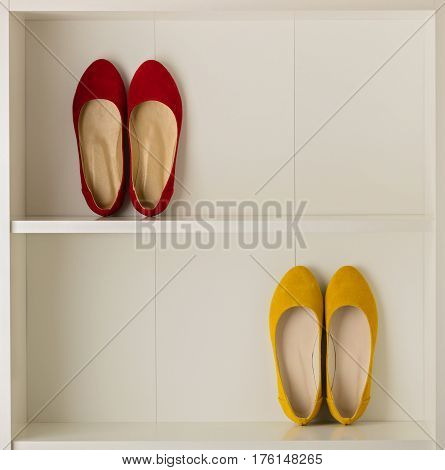 Women's shoes (ballet shoes) in the white wardrobe. Selective focus.