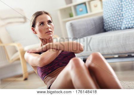 Fit girl doing sit-ups at home in the living room