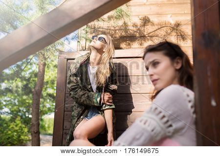 Young Trendy Woman Standing Outside In Sun With Her Friend