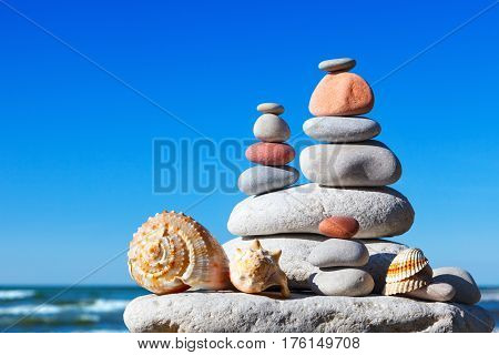 Pyramid of colorful rocks and shells on the sea background. The concept of peace and harmony