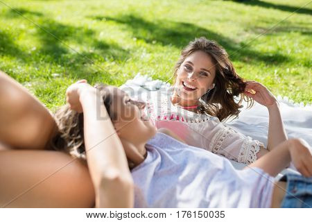 Two Pretty Women Lying Together At Park Laughing