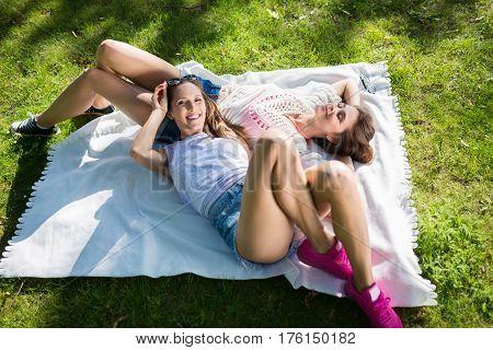 Happy Female Friends Relaxing On Blanket In Park