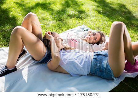 Pretty Happy Female Friends Lying On Blanket In Park