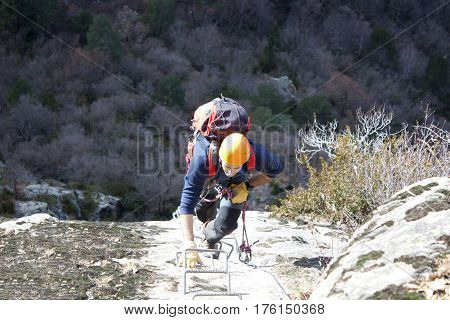 mountaineer doing a via ferrata with his backpack