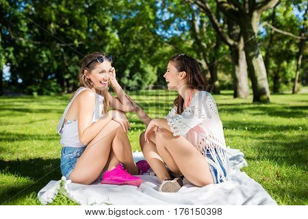 Candid friend chat on blanket in fresh air